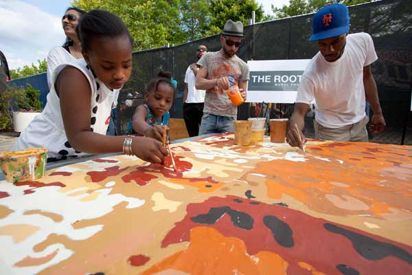 "<div class=""meta ""><span class=""caption-text "">The Roots Picnic Paint Day. Backstage at the fifth annual Roots Picnic, festival-goers help paint portions of The Roots mural, which will be installed on South Street, between Broad and 15th Streets.  (Photo by Steve Weinik)</span></div>"