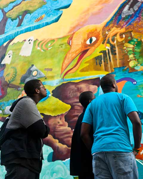 How to Turn Anything Into Something Else &copy; 2011 City of Philadelphia Mural Arts Program &#47; Miss Rockaway Armada. Miss Rockaway Armada collaborated with students from Mural Arts&#39; Art Education students to create this lyrical and vibrant mural about transformation.  At the dedication, students who helped paint the mural, look up at their work of art.   <span class=meta>(Photo by Steve Weinik)</span>