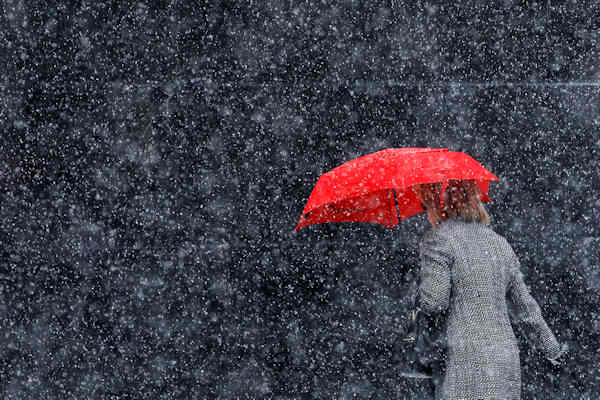 A woman walks along Broad Street during a winter storm, Sunday, Dec. 26, 2010, in Philadelphia. (AP Photo/Matt Slocum)