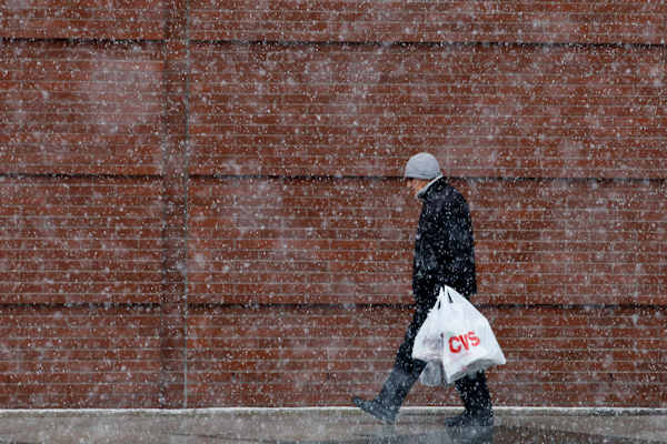 A shopper walks along Broad Street during a winter storm, Sunday, Dec. 26, 2010, in Philadelphia. (AP Photo/Matt Slocum)
