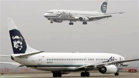 FILE - In this Jan. 17, 2009 file photo, an Alaska Airlines plane comes in for a landing as another taxis for takeoff at Seattle-Tacoma International Airport in Seattle. Alaska Airlines and its Horizon Air affiliate are canceling dozens of flights because their computer system failed. Company spokesman Paul McElroy says the two airlines canceled 60 flights by late Saturday morning, March 26, 2011, six hours after the outage started. (AP Photo/Ted S. Warren, File)