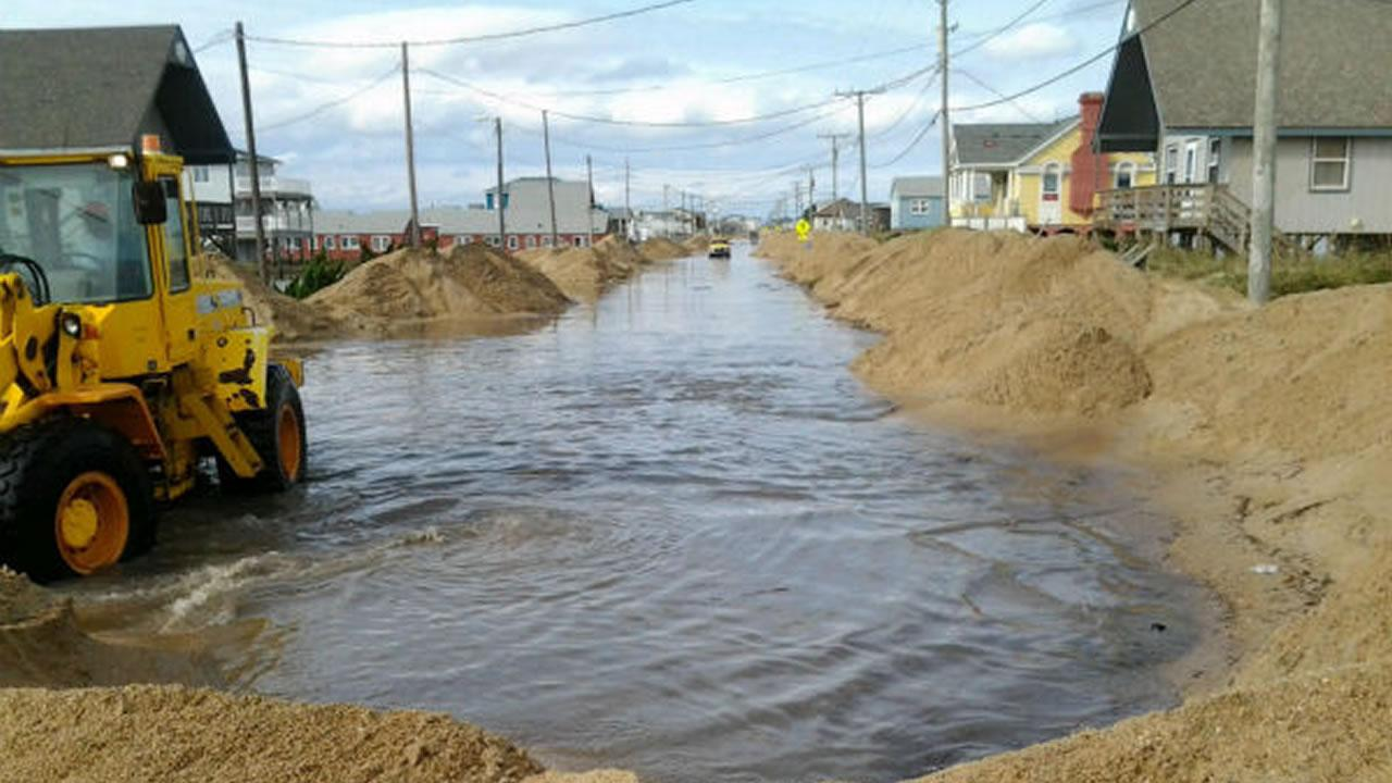 Workers scoop up sand and water covering NC Hwy 12 in Kitty Hawk. <span class=meta>(Jim Schumacher)</span>