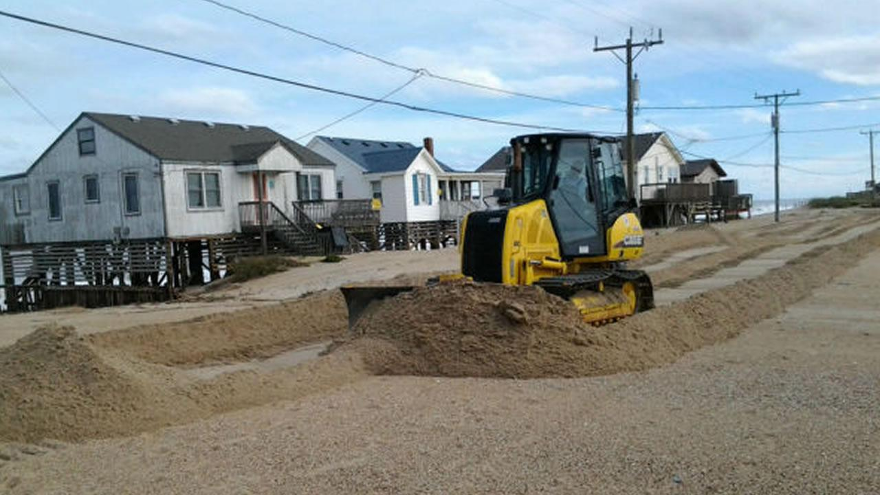 Workers scoop up sand and water covering NC Hwy 12 in Kitty Hawk.Jim Schumacher