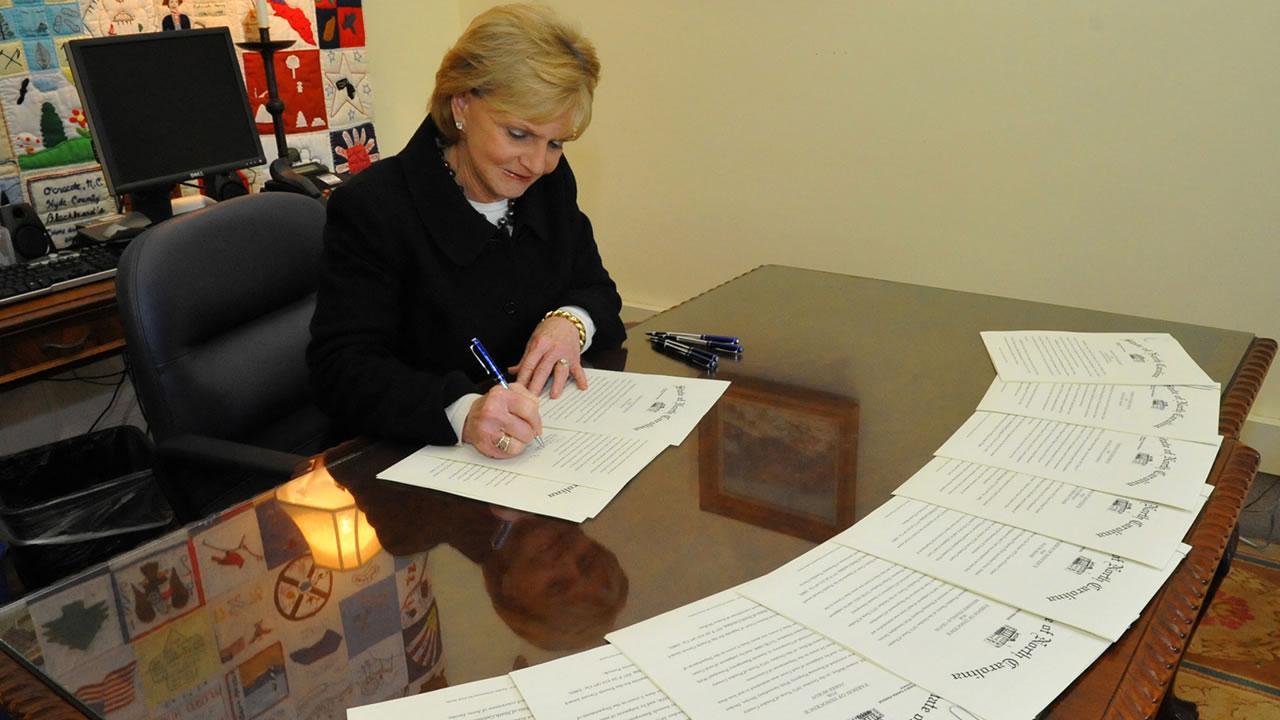 Governor Bev Perdue signs pardons for the Wilmington Ten