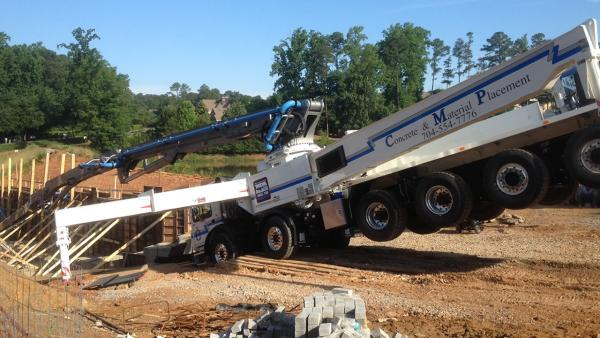 A concrete pumping truck toppled forward at a work site in Cary.