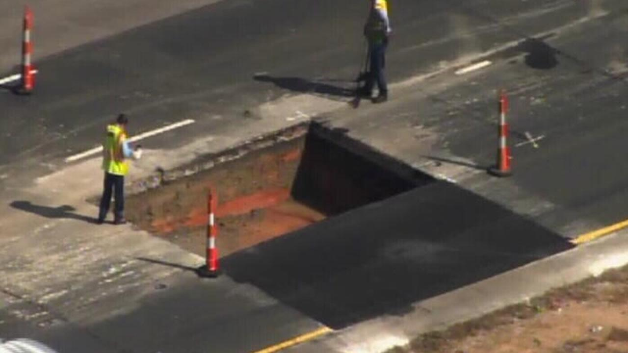Construction workers near a large hole cut into the highway pavement Thursday morning.