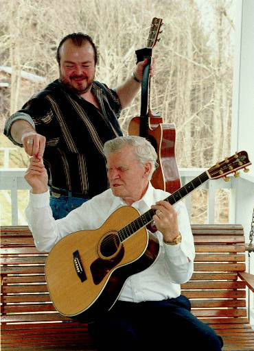 Richard Watson, top, hands his grandfather Doc Watson, a guitar pick, as the two play on the back porch of Doc's home in Deep Gap, N.C., March 15, 2000.  Richard Watson can barely play his own part for watching his grandfather's amazingly nimble fingers.  Richard almost missed the chance to learn from his grandfather.  Doc almost retired 15 years ago, heartbroken over the death of his son Merle, Richard's father, who died in a tractor accident at age 36.  Doc' love of music proved stronger than his grief and he returned to recording and touring.  (AP Photo/Karen Tam)