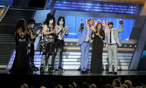 Musical group KISS presents the vocal group of the year award to musical group Lady Antebellum at the 47th Annual Academy of Country Music Awards on Sunday, April 1, 2012 in Las Vegas. From left, Eric Singer, Paul Stanley, Tommy Thayer, Charles Kelley, Hillary Scott and Dave Haywood. (AP Photo/Mark J. Terrill)
