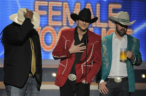 Ashton Kutcher, center, presents the award for female vocalist of the year at the 47th Annual Academy of Country Music Awards on Sunday, April 1, 2012 in Las Vegas. (AP Photo/Mark J. Terrill)