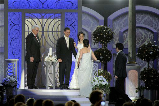 From left, Reverend Phil York marries Frank Tucci and Christina Davidson as Martina McBride and Pat Monahan perform onstage at the 47th Annual Academy of Country Music Awards on Sunday, April 1, 2012 in Las Vegas. (AP Photo/Mark J. Terrill)