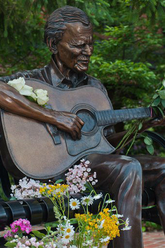 "In this photo provided by Mast General Store, flowers adorn a statue of Arthel ""Doc"" Watson in downtown Boone, N.C., on Friday, May 25, 2012. (AP Photo/Mast General Store, Lynn Willis)"