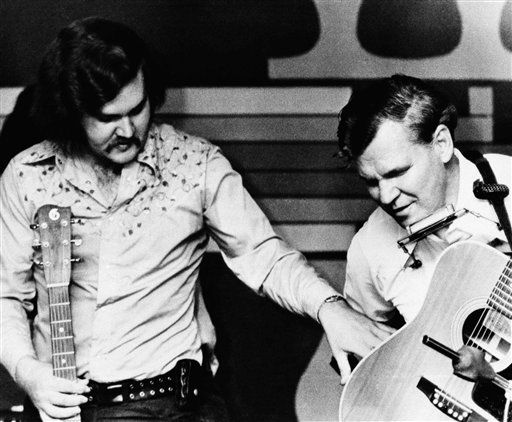 Doc Watson, right, and his son Merle brought their brand of country music out of the hollers of Deep Gap, N.C. during the folk revival of the 1960s,  May 29, 1974 in Nashville. Doc, blind from birth, felt sight has little to do with communicating with an audience. Music, he explained gently, bridges all kinds of gaps. (AP Photo)