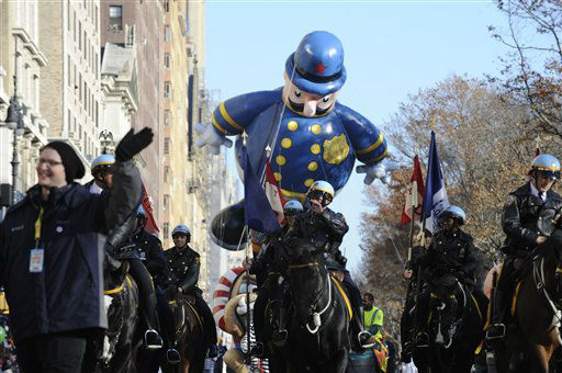 Mounted police lead a  policeman balloon as it...