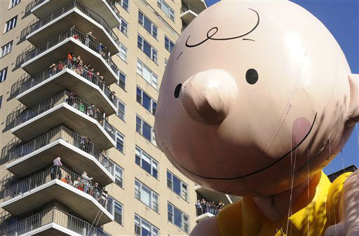 The Charlie Brown balloon passes people on...