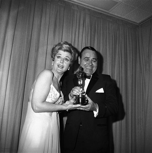 "<div class=""meta ""><span class=""caption-text "">Comedian Jonathan Winters accepts Oscar won by Peter Ustinov as best supporting actor of the year, presented by actress Angela Lansbury, April 5, 1965. Ustinov won for his role in ""Topkapi.""  (AP Photo)</span></div>"