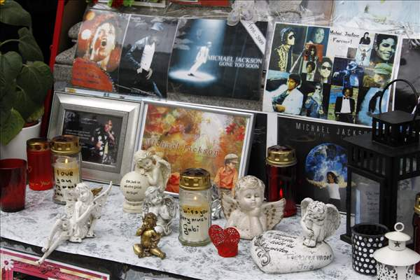 Candles and pictures are laid at a memorial for late US pop star Michael Jackson in Munich, southern Germany, on Thursday, June 24, 2010. German fans commemorated the first anniversary of the superstar's death. (AP Photo/Matthias Schrader)