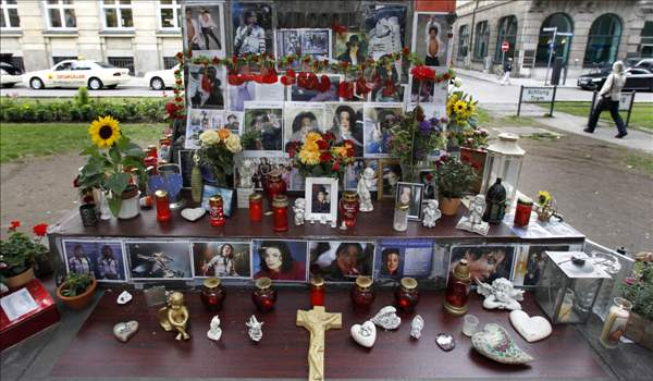 Candles, flowers and pictures are laid at a memorial for late US pop star Michael Jackson in Munich, southern Germany, on Thursday, June 24, 2010. German fans commemorated the first anniversary of the superstar's death. (AP Photo/Matthias Schrader)