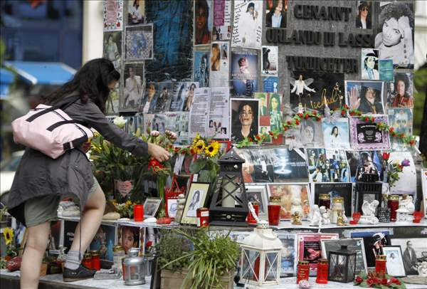 A woman places a tribute to the late US pop star Michael Jackson at a memorial in Munich, southern Germany, on Thursday, June 24, 2010. The death of Jackson, one year later, continues to captivate the world. (AP Photo/Matthias Schrader)