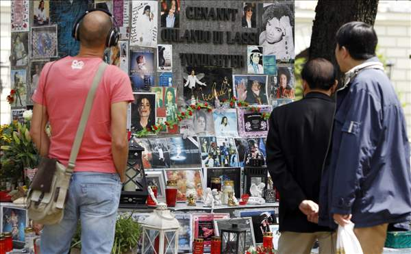 People look at a memorial for the late US pop star Michael Jackson in Munich, southern Germany, on Thursday, June 24, 2010. The death of Jackson, one year later, continues to captivate the world. (AP Photo/Matthias Schrader)