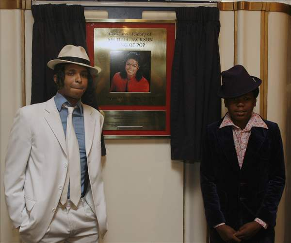 Performers of the 'Thriller Live' show Ricko Baird, left, and Mitchell Zhanghaza pose for photographers next to the special commemorative plaque to mark the anniversary of the death of U.S. performer  Michael Jackson, as it is unveiled at the Lyric Theatre in London's West End, Thursday, June 24, 2010. After his death on June 25, 2009,  the Lyric Theatre has become a focus for fans who created a shrine of flowers, candles, and tributes as it is the home to the 'Thriller Live' show celebrating the music of Jackson and the Jackson 5. (AP Photo/Akira Suemori)