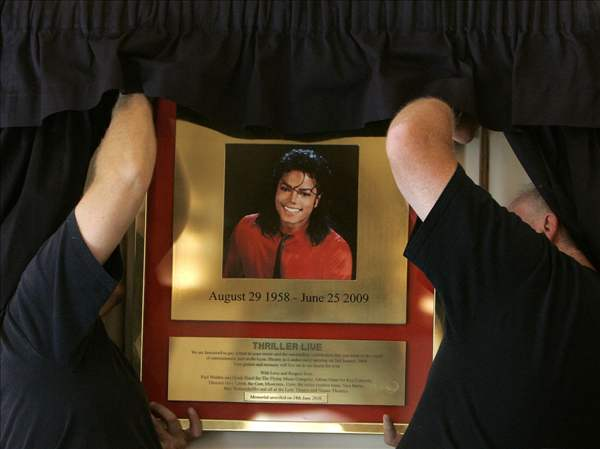Workers display the commemorative plaque to mark the anniversary of the death of U.S. performer  Michael Jackson, prior to it being unveiled, at the Lyric Theatre in London's West End, Thursday, June 24, 2010. After his death on June 25, 2009,  the Lyric Theatre has become a focus for fans who created a shrine of flowers, candles, and tributes as it is the home to the 'Thriller Live' show celebrating the music of Jackson and the Jackson 5. (AP Photo/Akira Suemori)