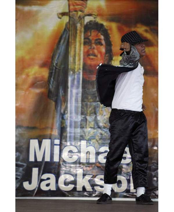 A Michael Jackson impersonator performs in front of a mural of the King of Pop during a tribute by former inmates on his first death anniversary Friday, June 25, 2010 at the Capitol Compound in Cebu city in central Philippines. (AP Photo)