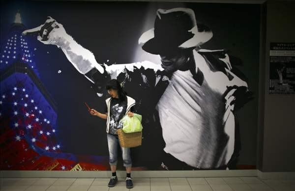 "A Michael Jackson fan stands in front of a giant poster of the King of Pop during the exhibition of ""Michael Jackson Official Life Time Collection"" ahead of his one year anniversary of his death in Tokyo, Friday, June 25, 2010. (AP Photo/Junji Kurokawa)"