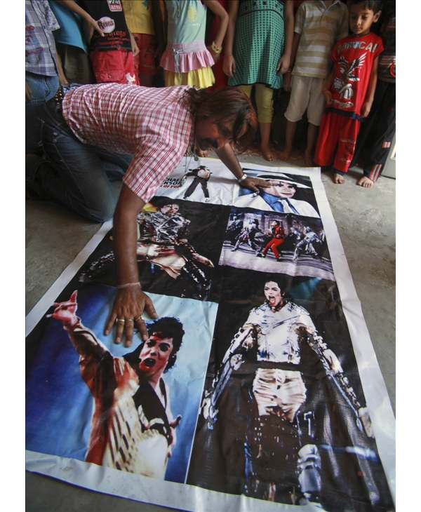 A Michael Jackson fan cleans his poster on his first death anniversary in Jammu, India, Friday, June 25, 2010. (AP Photo/Channi Anand)