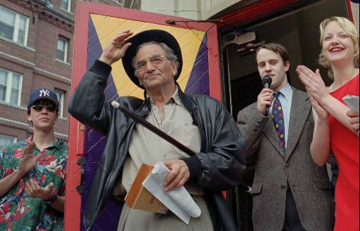 Actor Peter Falk, best known for his television portrayal of the detective Columbo, tips his hat to the crowd as he is recognized as Gentleman of the Year, 1996, by the members of the Harvard Lampoon, Monday, April 1, 1996, in Cambridge, Mass.  Harvard Lampoon members Dan Williams, left, John Abbott, second from right, and Rebecca Kirshner, right, look on.  <span class=meta>(AP Photo&#47; SUSAN WALSH)</span>