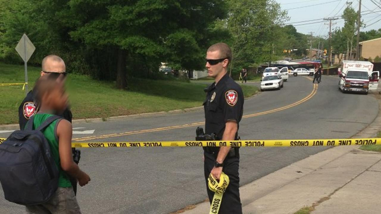 Police speak with a young bystander as they tape off a crime scene in Durham.