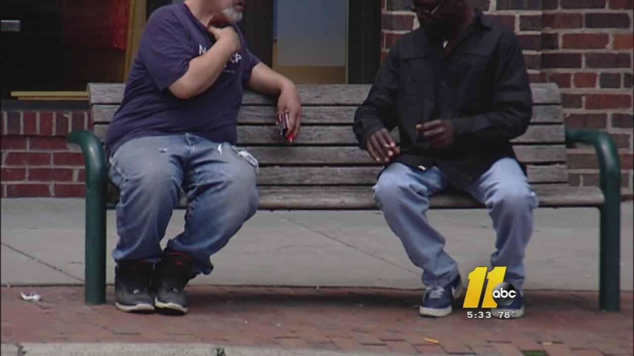 Homeless people sit on a bench on Franklin Street in Chapel Hill