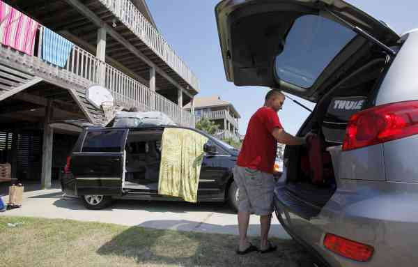Tim Childs, from Albany, N.Y., prepares to leave a vacation rental house in Avon, N.C., Wednesday, Sept. 1, 2010.  (AP Photo/Gerry Broome)