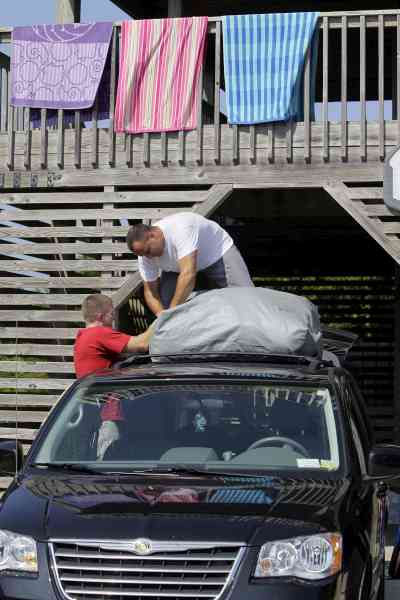 Tim Childs, left, and Robert Lindsay, from Albany, N.Y., prepare to leave their vacation rental house in Avon, N.C., Wednesday, Sept. 1, 2010.  (AP Photo/Gerry Broome)