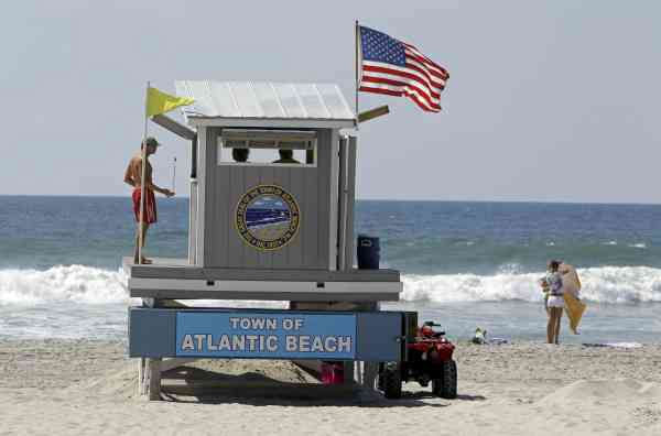 A lifeguard stands watch as sunbathers hit the beach in Atlantic Beach, N.C., Wednesday, Sept. 1, 2010.  (AP Photo/Chuck Burton)
