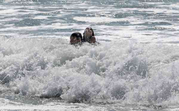 Rudi Hosp and his daughter Ethnee, 6, of Germany, ride the surf as Hurricane Earl headed toward the eastern coast in Atlantic Beach, N.C., Wednesday, Sept. 1, 2010. (AP Photo/Chuck Burton)