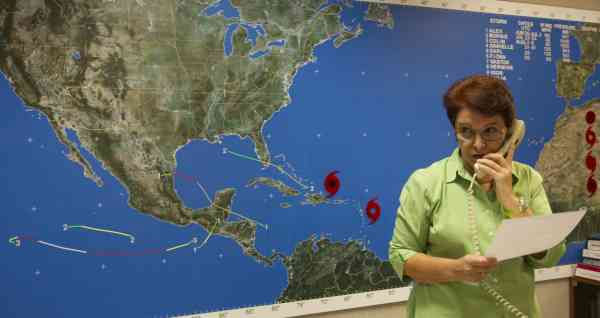 Gladys Rubio answers phone calls, at the National Hurricane Center in Miami, Wednesday, Sept. 1, 2010 as powerful Hurricane Earl wheeled toward the East Coast. (AP Photo/J Pat Carter)