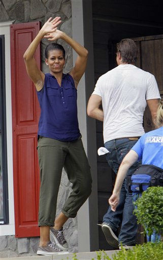 "<div class=""meta ""><span class=""caption-text "">First lady Michelle Obama waves as she enters the Jubilee House during the taping of Extreme Makeover Home Edition in Fayetteville, N.C., Thursday, July 21, 2011.   (AP Photo/ Gerry Broome)</span></div>"