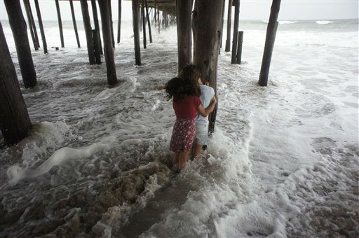 "<div class=""meta ""><span class=""caption-text "">Kaylan Davis, 7, and Acy Davis, 8, play under a pier during a storm surge caused by Hurricane Irene in Kill Devil Hills, N.C., Friday, Aug. 26, 2011 on North Carolina's Outer Banks. (AP Photo/ Charles Dharapak)</span></div>"