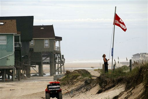 Erika Audfroid, a lifeguard with Nags Head Ocean Rescue, hoists a no swimming flag along the beach in Nags Head, N.C., Friday, Aug. 26, 2011 as hurrican Irene takes aim at the North Carolina coast.  The full force of Hurricane Irene was still a day away from the East Coast but heightened waves began hitting North Carolina&#39;s Outer Banks early Friday.   <span class=meta>(AP Photo&#47; Gerry Broome)</span>