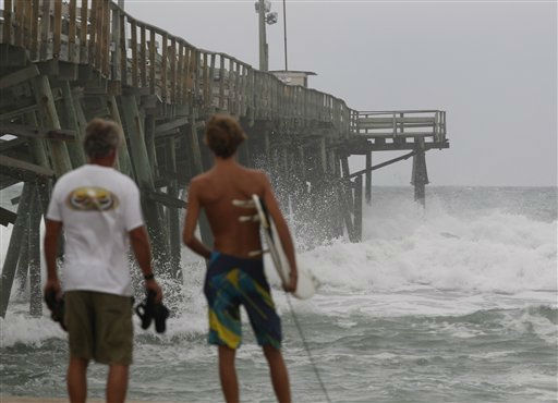 Surfers look at the waves crashing against the Oceana Pier in Atlantic Beach, N.C., Friday, Aug. 26, 2011 as Hurricane Irene heads toward the North Carolina coast. <span class=meta>(AP Photo&#47; Chuck Burton)</span>
