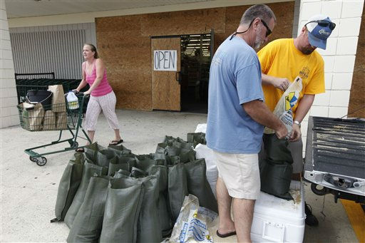 Jake Overton, right, and Jay Overton, second right, fill sand bags  in front of an open store with boarded up windows in anticipation of the arrival of Hurricane Irene in Nags Head, N.C., Friday, Aug. 26, 2011 on North Carolina&#39;s Outer Banks.  <span class=meta>(AP Photo&#47; Charles Dharapak)</span>