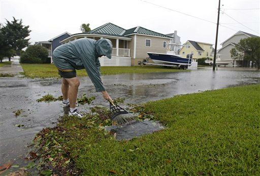 Chris Dagner clears storm debris from a storm drain to prevent more flooding near her house in Morehead City, N.C., Saturday, Aug. 27, 2011 as Hurricane Irene hit the North Carolina coast.  <span class=meta>(AP Photo&#47; Chuck Burton)</span>