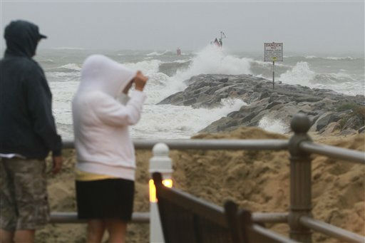 "<div class=""meta ""><span class=""caption-text "">Joyce Chase, of Chesapeake, Va., right, and Michael Minchew, look over the jetty at Rudee Inlet as the waves and rain from  Hurricane Irene hit Virginia Beach, Va., Saturday, Aug. 27, 2011. (AP Photo/ Steve Helber)</span></div>"