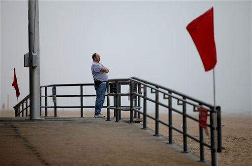 "<div class=""meta ""><span class=""caption-text "">Thomas Walker, of Merrick, N.Y., who runs a business on the Coney Island boardwalk, looks out over the adjacent closed beach as he and others await the arrival of Hurricane Irene, Saturday, Aug. 27 2011, in the Coney Island section of  New York.  (AP Photo/ Craig Ruttle)</span></div>"