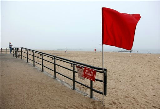 Thomas Walker, of Merrick, N.Y., far left, who runs a business on the Coney Island boardwalk, looks out over the adjacent closed beach as he and others await the arrival of Hurricane Irene, Saturday, Aug. 27 2011, in the Coney Island section of  New York.  <span class=meta>(AP Photo&#47; Craig Ruttle)</span>