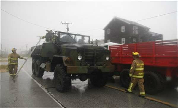 Using a military surplus truck fire fighters go from house to house fastening down gas tanks on the Outer Banks in Kitty Hawk, N.C., Saturday, Aug. 27, 2011 as Hurricane Irene reaches the North Carolina coast.  <span class=meta>(&#40;AP Photo&#47;Charles Dharapak&#41;)</span>