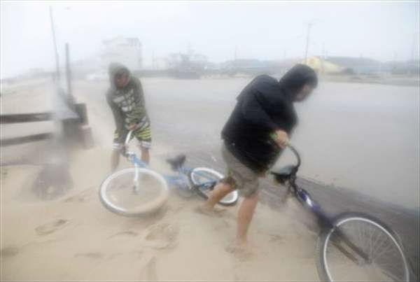 Two unidentified boys get back on their bikes as they leave the beach while being blasted with sand and rain from strong winds on the Outer Banks in Kill Devil Hills, N.C., Saturday, Aug. 27, 2011 as Hurricane Irene reaches the North Carolina coast. <span class=meta>( &#40;AP Photo&#47;Charles Dharapak&#41;)</span>