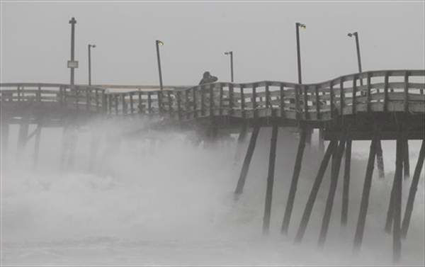Denis Hromin, a concerned fisherman, checks on Avalon Fishing Pier as it lost some pilings after being battered by wind and waves on the Outer Banks in Kill Devil Hills, N.C., Saturday, Aug. 27, 2011 as Hurricane Irene reaches the North Carolina coast. <span class=meta>( &#40;AP Photo&#47;Charles Dharapak&#41;)</span>