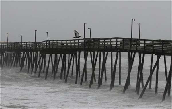 A bird flies over Avalon Fishing Pier as it is battered by wind and waves on the Outer Banks in Kill Devil Hills, N.C., Saturday, Aug. 27, 2011 as Hurricane Irene reaches the North Carolina coast.  <span class=meta>(&#40;AP Photo&#47;Charles Dharapak&#41;)</span>