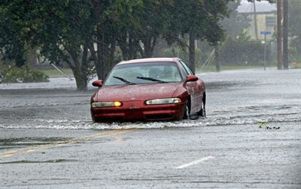 A man drives his car through a flooded street in New Bern, N.C., Saturday, Aug. 27, 2011 as Hurricane Irene hits the North Carolina coast. Hurricane Irene knocked out power and piers in North Carolina, clobbered Virginia with wind and churned up the coast Saturday to confront cities more accustomed to snowstorms than tropical storms. <span class=meta>( &#40;AP Photo&#47;Chuck Burton&#41;)</span>